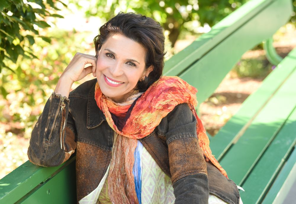 Mandana Varnoos smiles while sitting outside on a bench