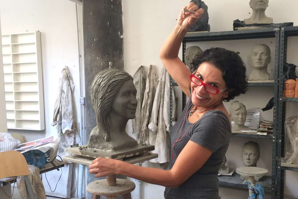 Mandana Varnoos smiles while working with clay in her studio.