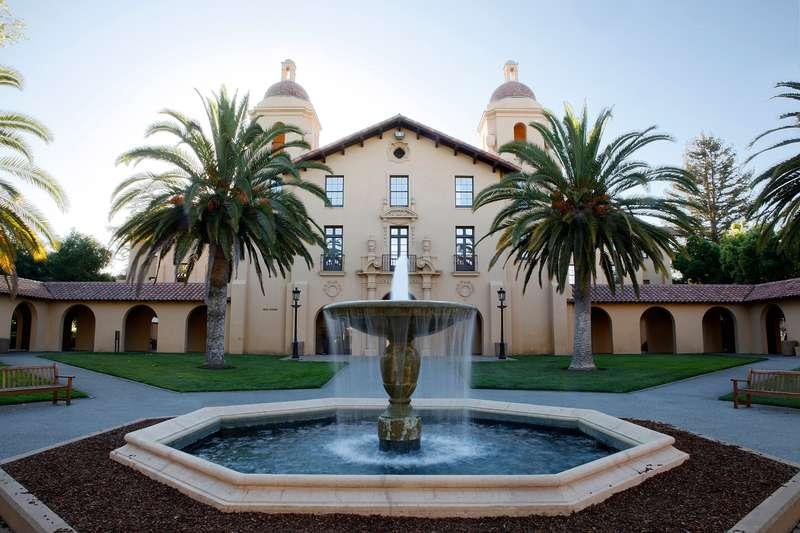 Water fountain, palm trees, and building on Stanford campus