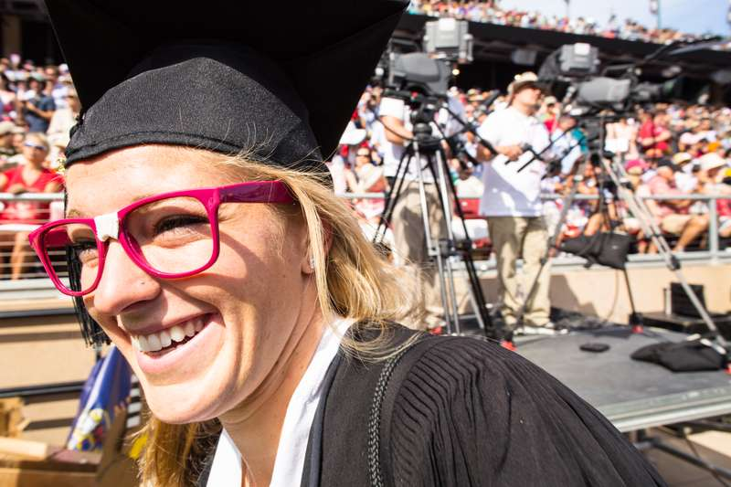 Female Stanford student wearing pink glasses and a cap and gown at graduation