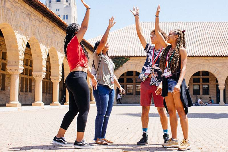 Group of Black Stanford students raise hands in cheer